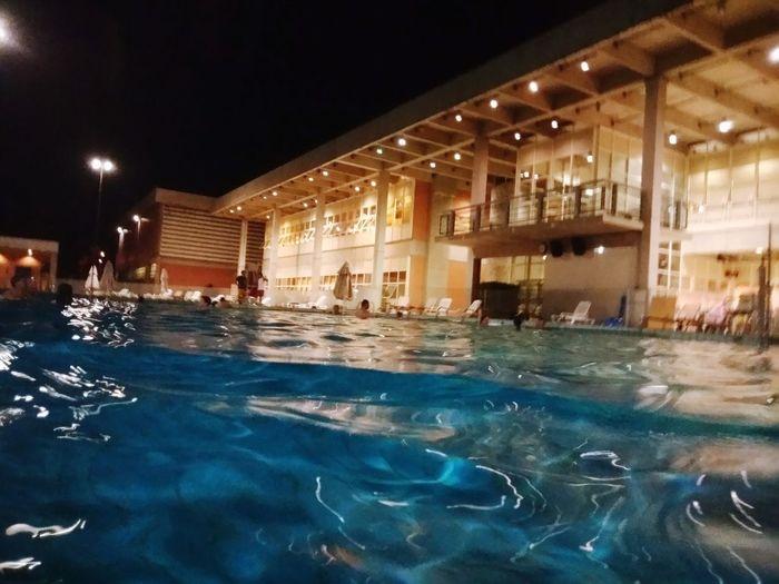 Swimming pool in illuminated building at night