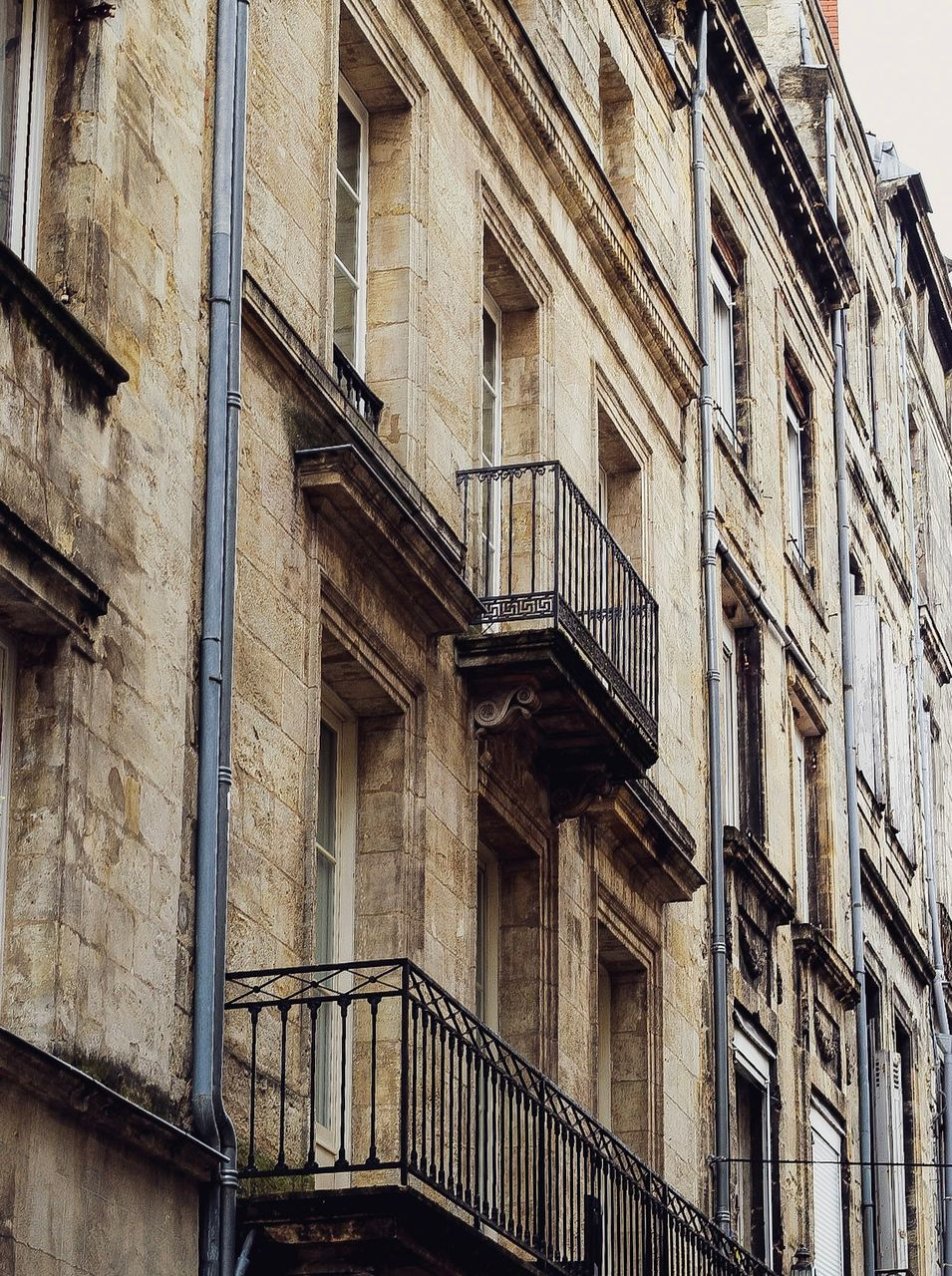 architecture, built structure, low angle view, building exterior, building, no people, window, day, railing, old, residential district, outdoors, city, staircase, full frame, backgrounds, fire escape, pattern, balcony, the past, apartment
