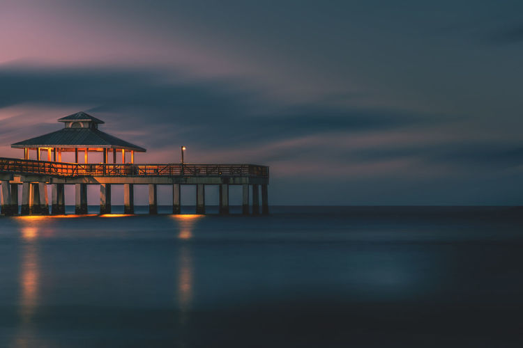Illuminated built structure over sea against cloudy sky at dusk
