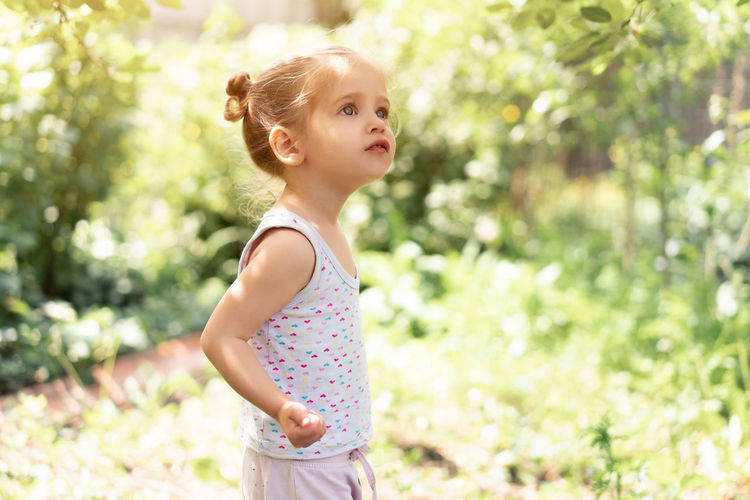 Girl looking away while standing against plants