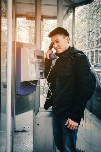 Man using telephone in city