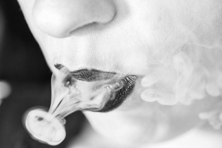 Close-up of woman exhaling smoke