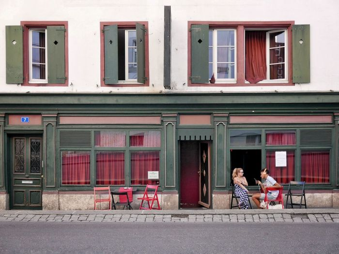 Woman sitting on street against building in city