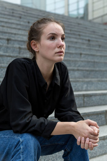 Young woman sitting on staircase One Person Casual Clothing Jeans Staircase Caucasian Young Woman Young Adult Outdoors Outside Natural Lighting Sitting Three Quarter Length Real People Side View Looking Away Contemplation Posing Hands Clasped