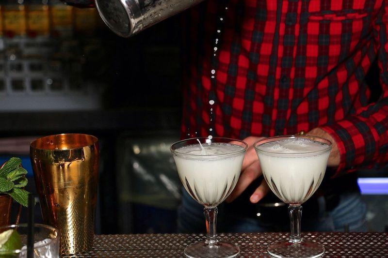 Midsection Of Bartender Making Cocktails