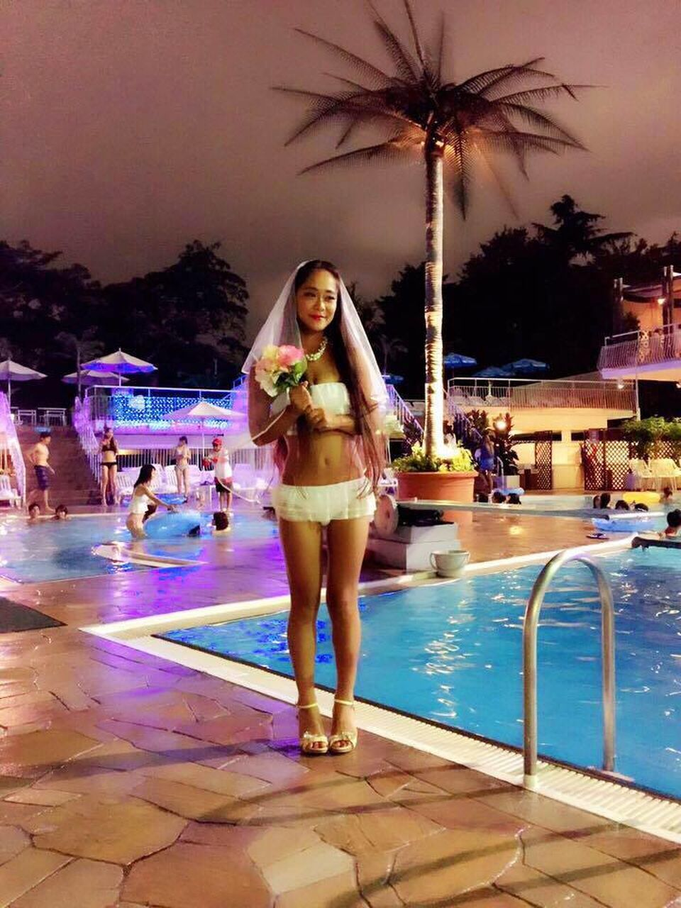 swimming pool, young adult, lifestyles, real people, young women, illuminated, leisure activity, front view, night, portrait, full length, looking at camera, water, tree, outdoors, one person, beautiful woman, palm tree, architecture, adult, people