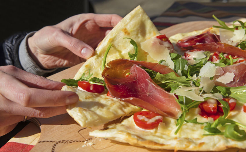 Flammekueche, Flammkuchen, tarte flambée is pizza style Alsace, Alsatian-Mosellan and South German dish composed of bread dough rolled out very thinly with prosciutto ham and rocca salad and slices of cheese. It is one of the most famous specialties of the region. Cuisine Dishes Fast Food Flammekuech German Pizza Time Tarte Flambee Close-up Flammkuchen Food Food And Drink Freshness Holding Human Body Part Human Hand One Person Outdoors Outside Pizza Prosciutto Ready-to-eat SLICE Tasty