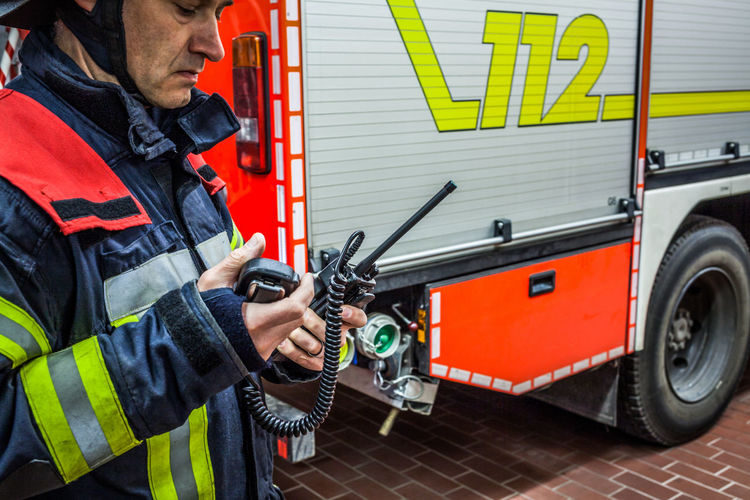 Firefighter using walkie-talkie by fire engine