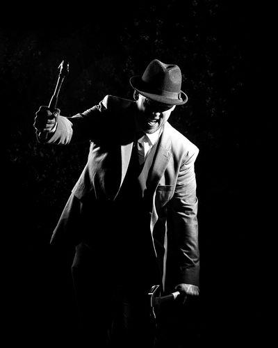 Mafia Holding Hammers Against Black Background