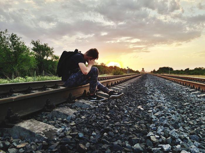 Man lying down on railroad track against sky