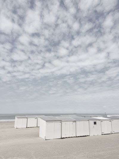 Beach huts on sand against sky