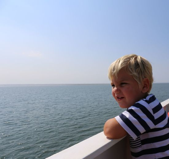 Boy smiling by sea against sky