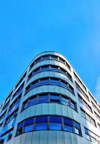 Low angle view of modern building against blue sky