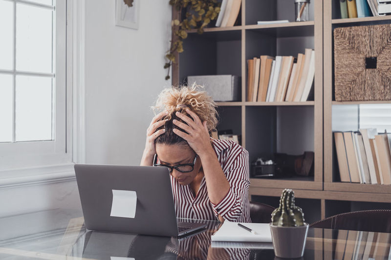 Depressed woman sitting by laptop in office