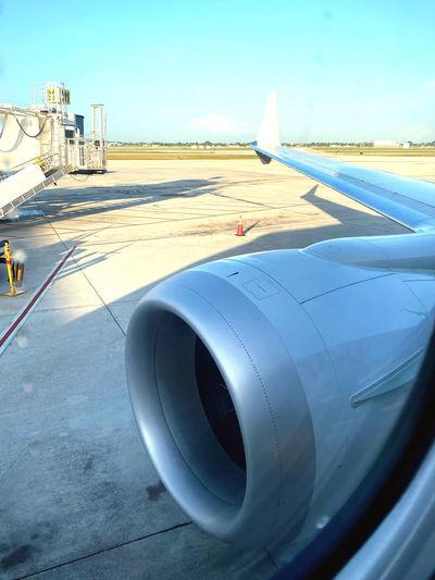 Airplane flying over airport runway against sky