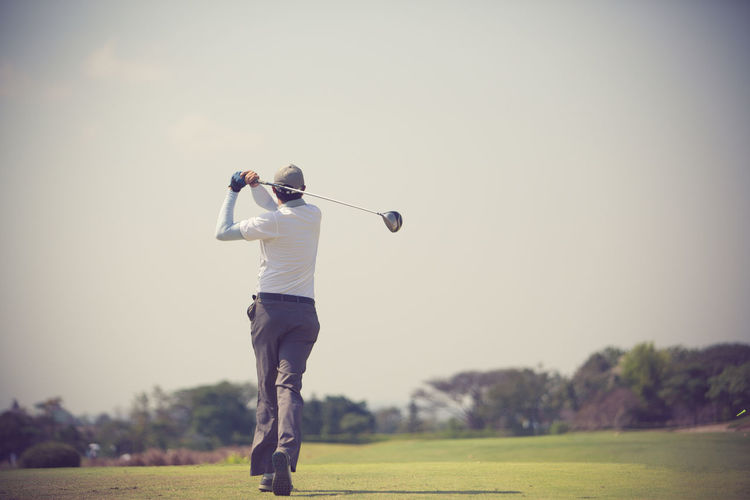 Rear view of golfer playing on field against clear sky