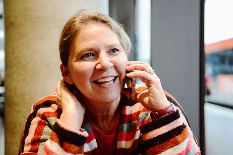Close-up of smiling mature woman using mobile phone at cafe