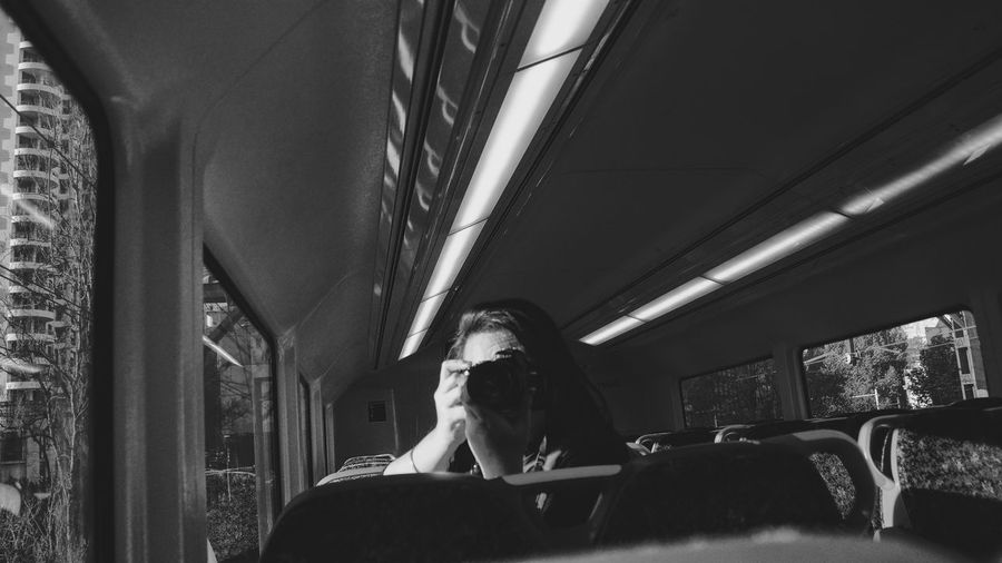 Woman photographing through camera while traveling in bus
