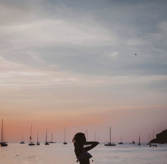 Silhouette person on sailboat in sea against sky during sunset