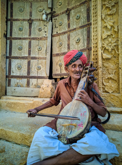 Aged Old Local Musician Musician Plucking An Instrument Musical Instrument Guitar Smiling Sitting Happiness Music Headwear Playing Street Musician Entertainment Occupation Music Style  HUAWEI Photo Award: After Dark #urbanana: The Urban Playground Be Brave The Art Of Street Photography