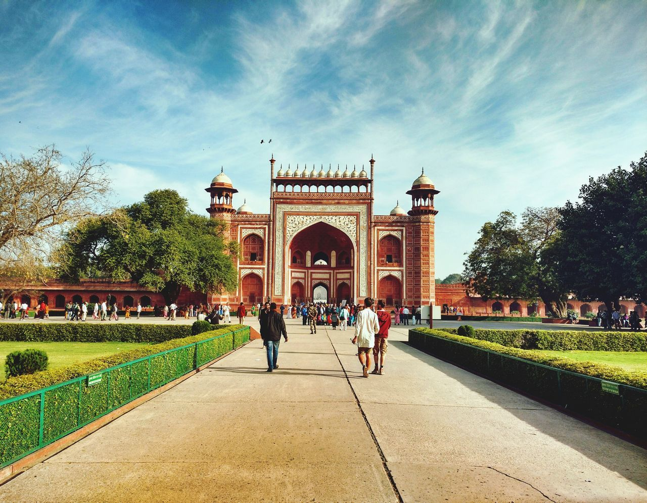 built structure, architecture, large group of people, travel destinations, tree, arch, tourism, day, building exterior, real people, history, sky, outdoors, cloud - sky, leisure activity, vacations, grass, lifestyles, triumphal arch, men, nature, people