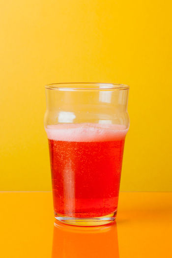 Close-up of beer in glass against yellow background