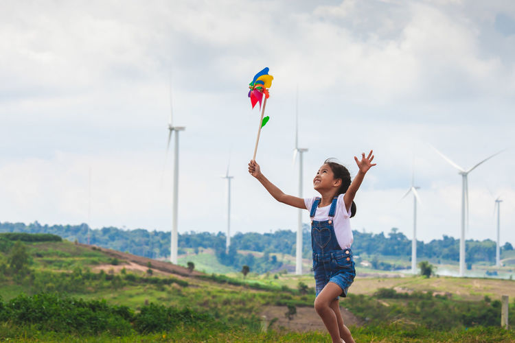 Girl playing with pinwheel toy on land with windmills in background