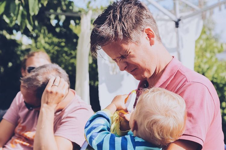 Fatherhood Moments Holding Leisure Activity Lifestyles Togetherness Focus On Foreground Child Father And Son Fatherhood  Outdoors Spraying Water Person Casual Clothing Young Adult Day