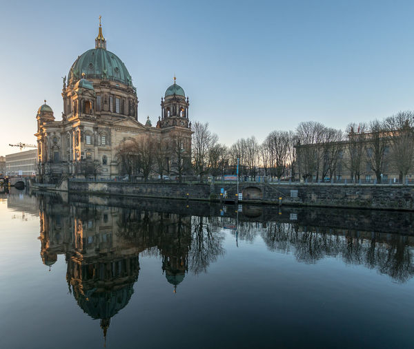 Reflection of berlin cathedral on spree river against clear sky