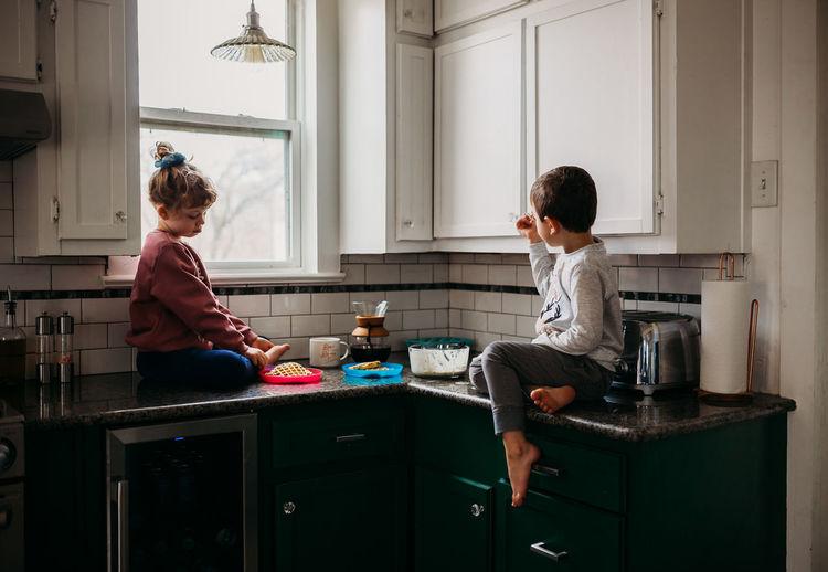 Full length of siblings sitting at home