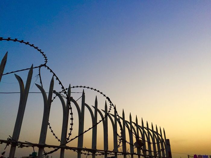 Razor wire fence against sky during sunset