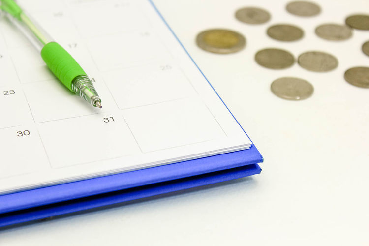 High angle view of calendar with coins on table