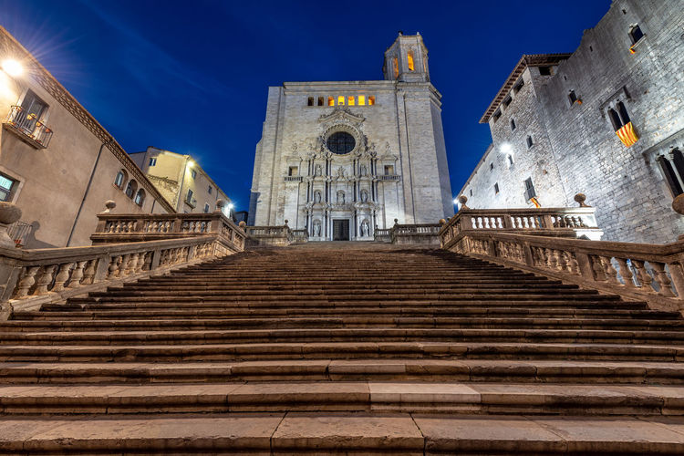 Low angle view of steps leading towards church amidst buildings against blue sky