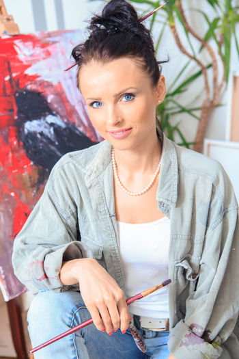 Portrait of smiling artist painting while sitting against wall at home