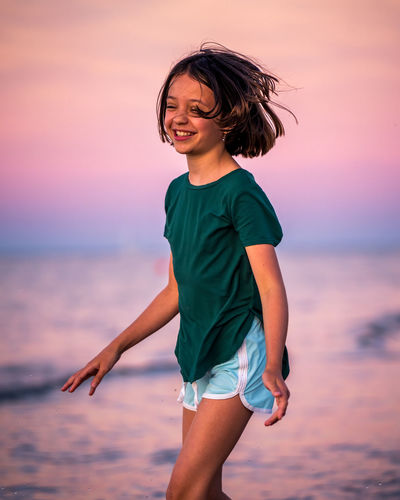 Young woman standing against sea during sunset