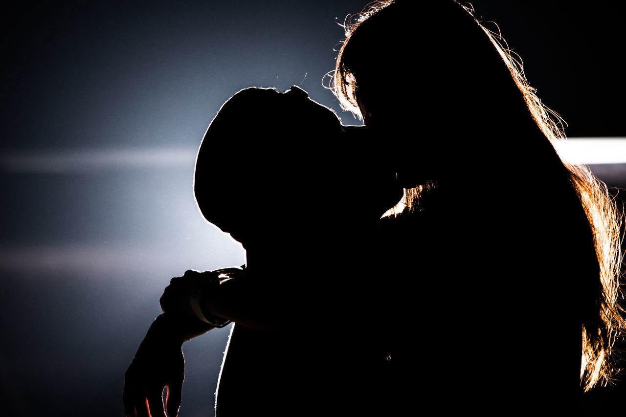 Silhouette man and woman kissing at night