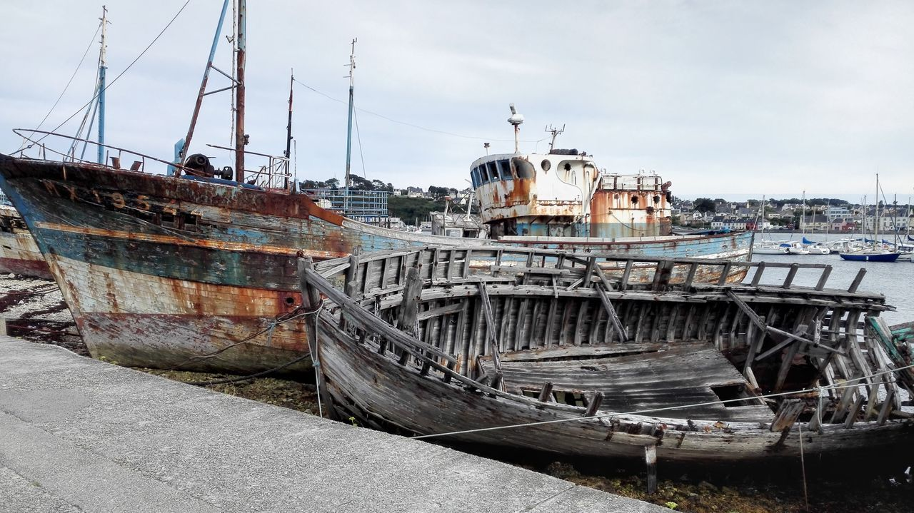 nautical vessel, abandoned, transportation, boat, moored, mode of transport, outdoors, sky, no people, damaged, ship, day, sea, harbor, water, shipyard