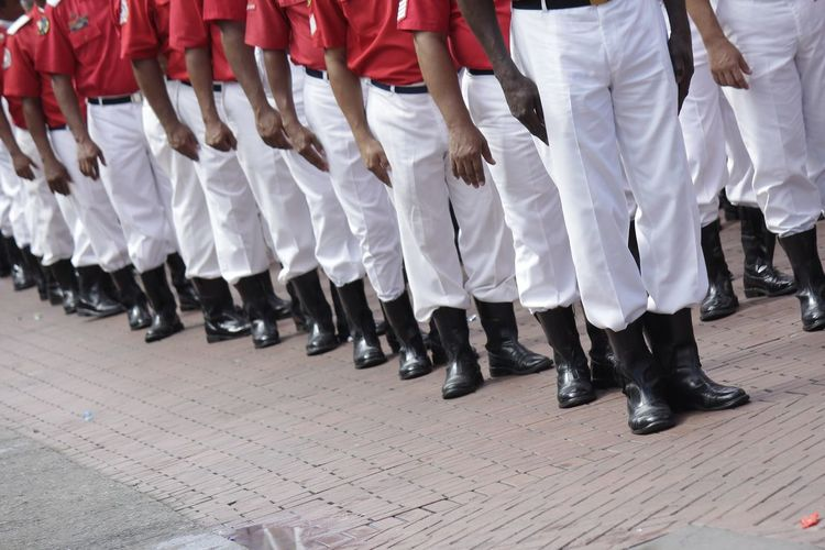 Low section of men wearing uniform while standing in row on street