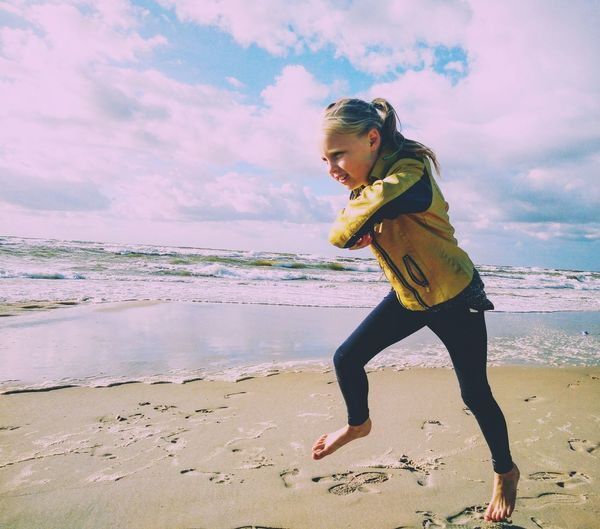 Girl Jogging On Beach Against Sky During Sunny Day