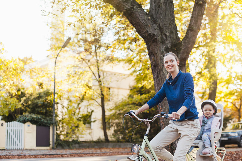 Happy man riding bicycle on autumn leaves