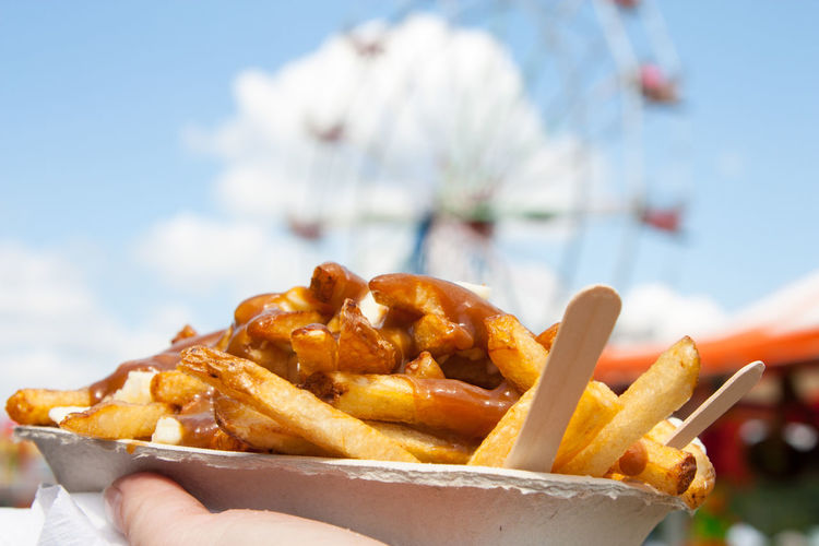 Close-up Concession Stand Day Deep Fried  Fall Fair Fashion Fast Food Ferris Wheel Festival Festival Season Focus On Foreground Food Food And Drink Food Truck French Fries Freshness Holding Human Hand Indulgence Midway Outdoors Poutine Snack Take Out Food Unhealthy Eating
