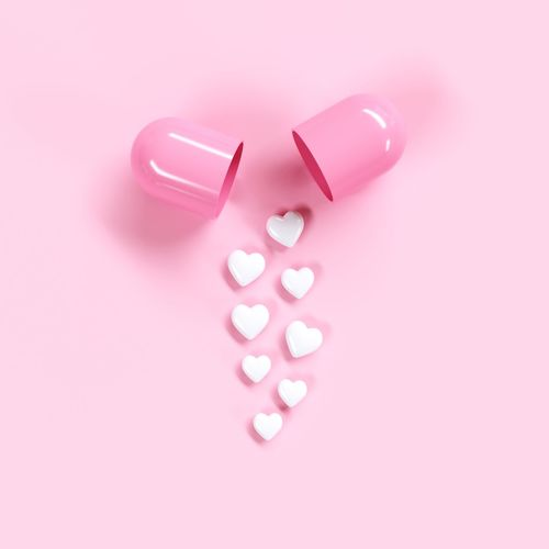 High angle view of heart shape pills by capsule against pink background