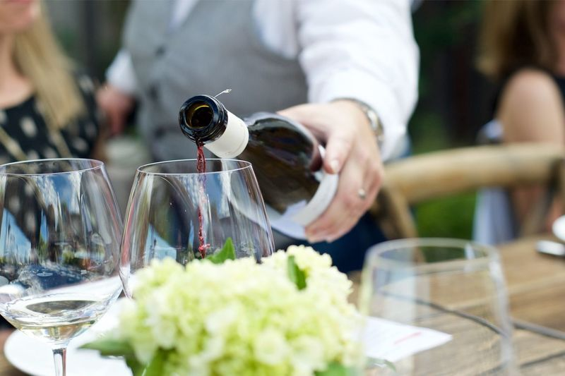 Cropped image of hand pouring wine in glass