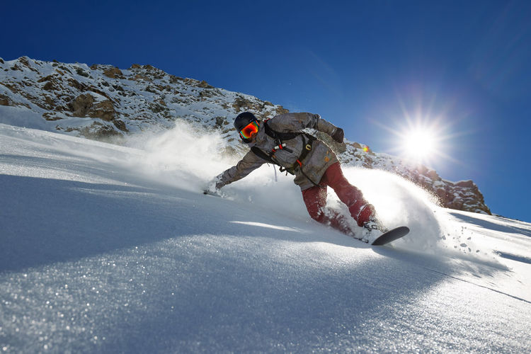 Sunshine riding Adult Adventure Cold Temperature Day Extreme Sports Full Length Headwear Helmet Leisure Activity Low Angle View Men Motion One Man Only One Person Only Men Outdoors Ski Goggles Skill  Snow Snowboarding Sport Sun Sunlight Winter Winter Sport