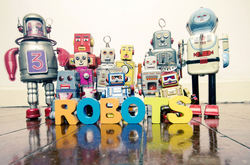 the word ROBOT with retro robot toys Fun Kindergarten Reflection Robots Teamwork Text Tin Toys Word Close-up Collection Education Large Group Of Objects Multi Colored No People Preschooler Robot Still Life Togetherness Toy Toy Robots Wooden Floor
