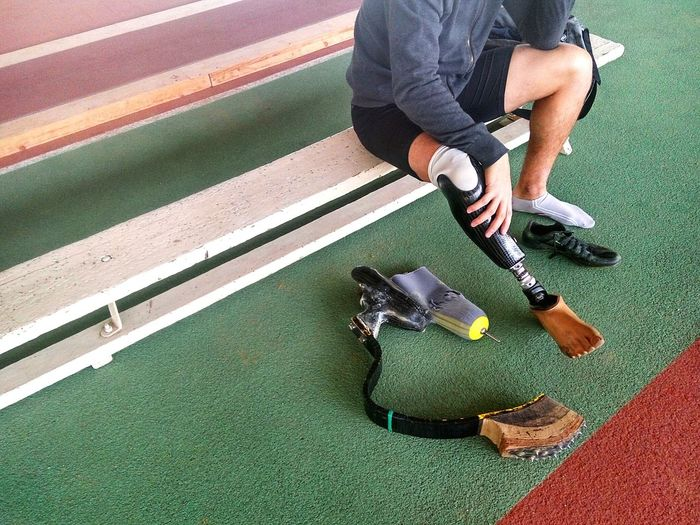 Low section of athlete with prosthetic leg sitting at running track