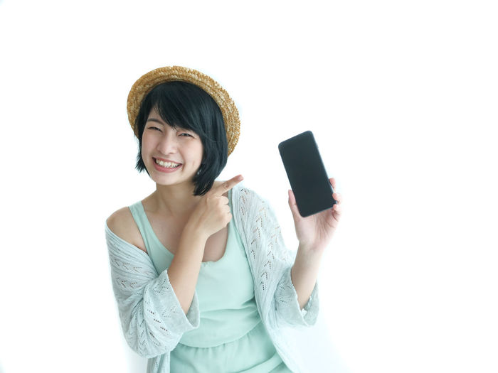 Portrait of smiling young woman using mobile phone against white background