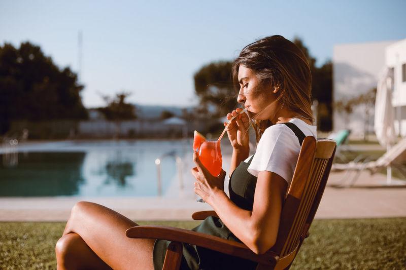 Woman sitting by swimming pool in lake