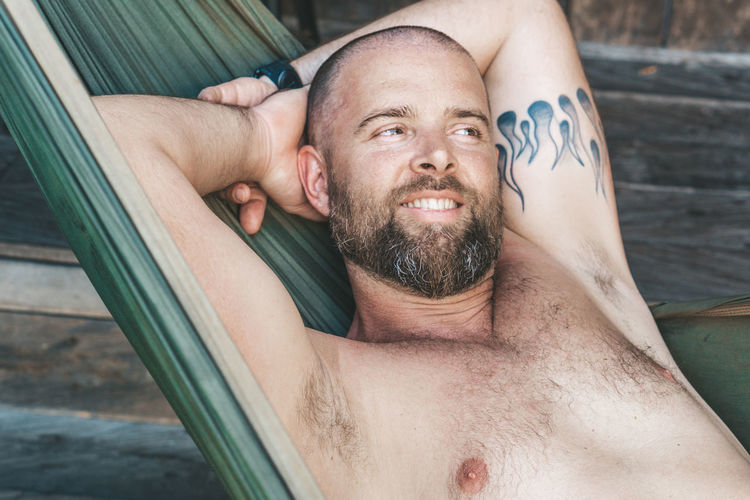 relaxing in hammock Real People One Person Beard Men Facial Hair Mature Adult Portrait Males  Mature Men Adult Shirtless Lying Down Leisure Activity Looking At Camera Lifestyles Mid Adult Men Smiling Relaxation Hands Behind Head Outdoors Mustache Hanging Out Bearded Thinking