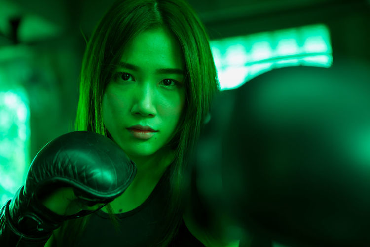 Portrait of woman boxing at gym